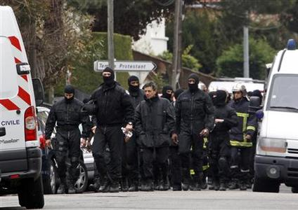 Masked French special unit policemen (RAID) leave the scene after the assault to capture gunman Mohamed Merah during a raid on a five-storey building to arrest a suspect in the killings of three children and a rabbi on Monday at a Jewish school, in Toulouse March 22, 2012. REUTERS/Jean-Paul Pelissier