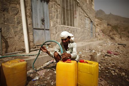 A man fills up jerry cans with water from a public tap in the western Yemeni province of Houdieda March 13, 2012. REUTERS/Khaled Abdullah