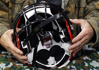 A worker assembles a Xenith football helmet at the company's facility in Lowell, Massachusetts March 26, 2012. REUTERS/Brian Snyder