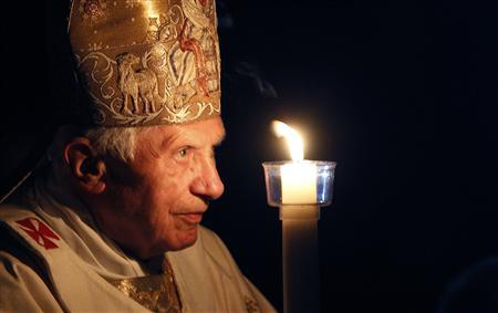 Pope Benedict XVI prays while holding a candle light as he arrives to lead a vigil mass during Easter celebrations at St. Peter's Basilica in the Vatican April 7, 2012. REUTERS/Alessandro Bianchi