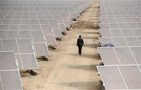 A man walks through solar panels at a solar power plant under construction in Aksu, Xinjiang Uyghur Autonomous Region April 5, 2012. REUTERS/Stringer