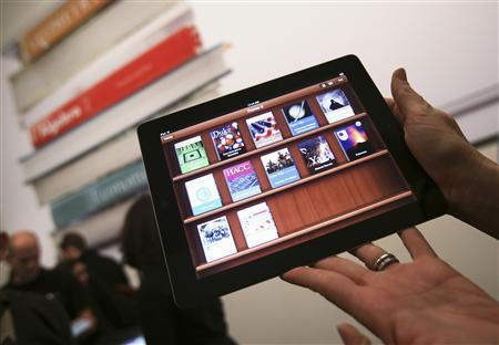 A woman holds up an iPad with the iTunes U app after a news conference introducing a digital textbook service in New York in this January 19, 2012, file photo. Apple Inc and several major publishers were accused by the U.S. government of conspiring to fix prices of e-books and limit retail price competition, according to a lawsuit filed on April 11, 2012. Picture taken January 19, 2012. REUTERS/Shannon Stapleton/Files