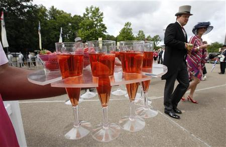 Race-goers pass by a tray of pink champagne on the fifth day of racing at Royal Ascot in southern England June 18, 2011. REUTERS/Suzanne Plunkett