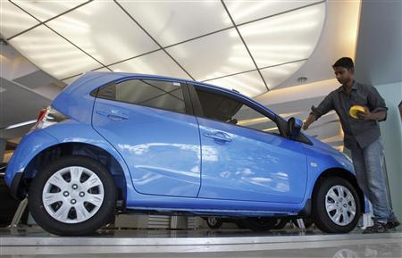 A showroom attendant polishes a Honda Brio car in Mumbai April 16, 2012. REUTERS/Vivek Prakash