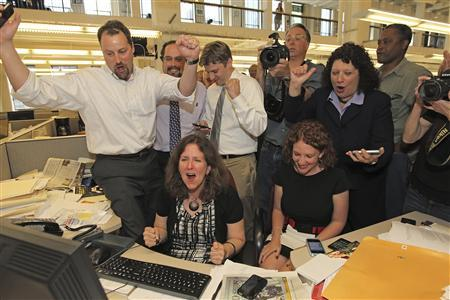 Members of the Philadelphia Inquirer staff react to learning of their Pulitzer Prize for Public Service from their series on School Violence in Philadelphia April 16, 2012. REUTERS/Michael Bryant/Philadelphia Inquirer/Handout.