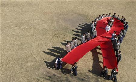 School children make an AIDS logo during the preparation for the World AIDS Day program at a school in the northern Indian city of Chandigarh November 29, 2006. REUTERS/Ajay Verma