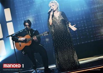 Iranian music star Googoosh (R) performs on stage with guitarist Babak Saeedi during the season finale of ''Googoosh Music Academy,'' a music competition show on Persian-language entertainment channel Manoto 1, in London in this handout taken November 2011. Launched in 2010, family-owned satellite channel Manoto 1's programming has struck a chord inside Iran and gained what is likely to be millions of fans since launching in 2010, though it is periodically jammed by Iran's Islamic government. The channel was launched by Kayvan and Marjan Abbassi, an Iranian couple, and focuses on entertainment and youth culture. REUTERS/Manoto/Handout