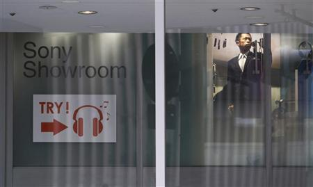An employee of Sony Corp is seen through a window at its company showroom in Tokyo January 21, 2009. REUTERS/Kim Kyung-Hoon