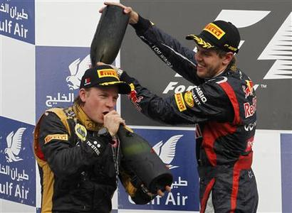 Winner Red Bull Formula One driver Sebastian Vettel of Germany pours champagne on second placed Lotus F1 Formula One driver Kimi Raikkonen of Finland during the podium ceremony after the Bahrain F1 Grand Prix at the Sakhir circuit in Manama April 22, 2012. REUTERS/Steve Crisp