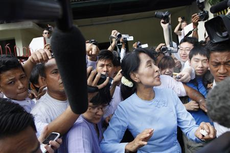 Myanmar pro-democracy leader Aung San Suu Kyi (R) leaves her office after a meeting in front of the National League for Democracy Party head office Yangon April 22, 2012. REUTERS/Minzayar