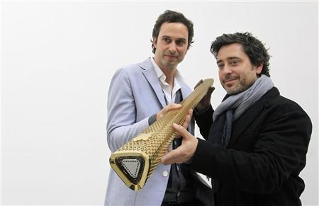 British designers Edward Barber (L) and Jay Osgerby hold the London 2012 Olympic Torch during Milan Design Week April 16, 2012. REUTERS/Alessandro Garofalo