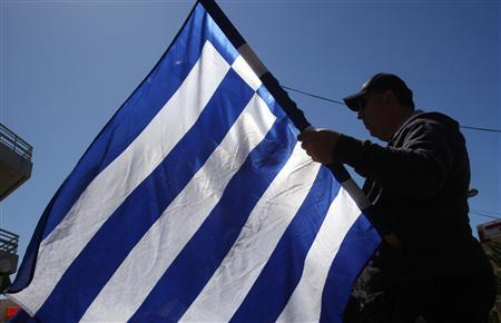 A member of the extreme right Golden Dawn party holds a Greek flag during an election campaign rally in Athens April 21, 2012. REUTERS/Yannis Behrakis