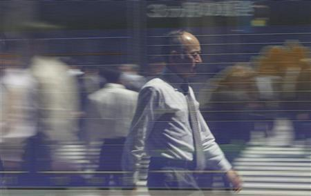 A man is reflected on a stock quotation board outside a brokerage in Tokyo April 24, 2012. REUTERS/Toru Hanai