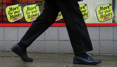 A woman walks past offers advertised in the windows of a supermarket near Manchester, April 25, 2012. REUTERS/Phil Noble