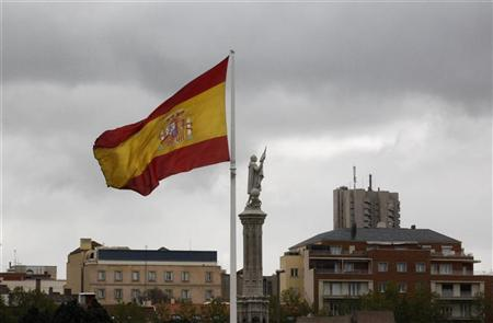 A Spanish flag flutters in the wind near a statue of Columbus in Madrid, April 19, 2012. REUTERS/Andrea Comas