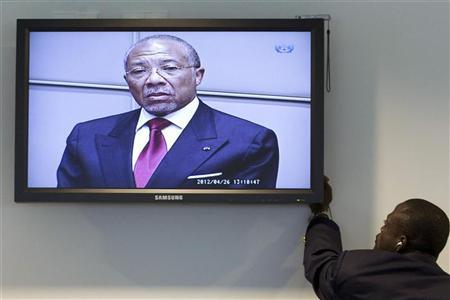 A journalist records the verdict of the judges during the trial of former Liberian President Charles Taylor (top, on screen), as he stands in the court room of the Special Court for Sierra Leone in Leidschendam, near The Hague, April 26, 2012. REUTERS/Peter Dejong/Pool