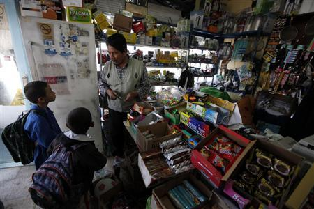Abdulkerim Turkmen talks with children at his grocery shop in Ovakent village March 27, 2012. REUTERS/Osman Orsal