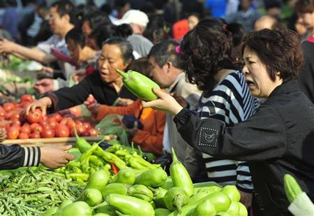A customer (R) bargains with a vendor for eggplants at an open-air food market in Shenyang, Liaoning province May 11, 2012. China's annual consumer inflation moderated in April despite strong food price rises, data on Friday showed, potentially giving Beijing more scope to loosen policy to help the economy rebound from a first-quarter slowdown in growth. REUTERS/Sheng Li