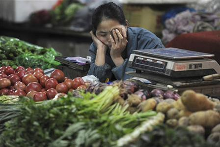 A vender naps as she waits for customers at a market in Hefei, Anhui province May 11, 2012. REUTERS/Stringer