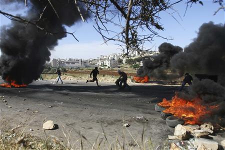 Palestinian protesters burn tyres during clashes with Israeli security officers at a demonstration held in solidarity with prisoners on hunger strike, outside Ofer prison near the West Bank city of Ramallah May 11, 2012. REUTERS/Mohamad Torokman