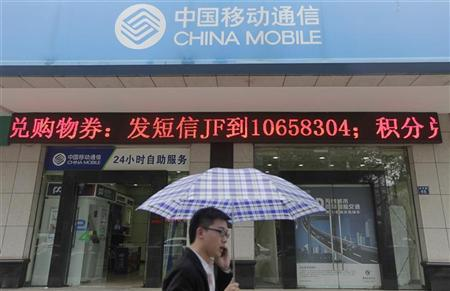 A man walks past a branch of China Mobile as he talks on his mobile phone on a rainy day in Wuhan, Hubei province April 20, 2012. REUTERS/Stringer