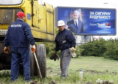 Men work in front of a campaign billboard of former Serbian President Boris Tadic in Belgrade May 16, 2012. REUTERS/Ivan Milutinovic