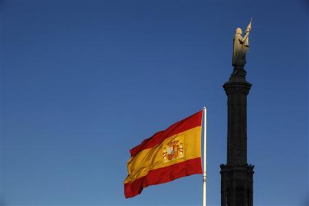 A Spanish flag flutters in the wind near a statue of Columbus in Madrid May 18, 2012. REUTERS/Susana Vera