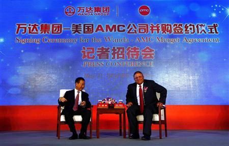 Gerry Lopez (R), chief executive of AMC Entertainment, sits next to Wang Jianlin, president of Wanda Group, before the start of a media conference after an official signing ceremony in Beijing May 21, 2012. REUTERS/David Gray