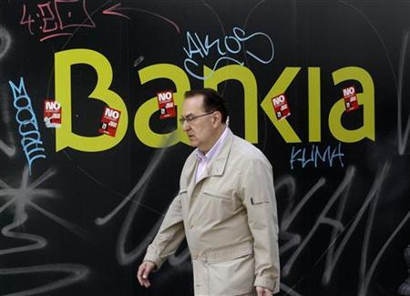 A man walks past the Bankia bank foundation in Madrid May 25, 2012. REUTERS/Andrea Comas