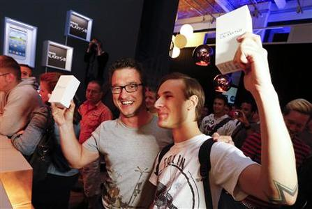 Customers pose for the media after they were first in line to buy Samsung Electronics' new Samsung Galaxy SIII smartphones during a late night sale event in Berlin May 28, 2012. REUTERS/Fabrizio Bensch