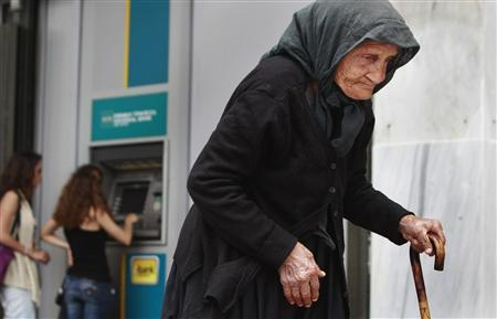 A woman makes her way by as people make a transaction at an ATM machine outside a National Bank branch in central Athens May 29, 2012. REUTERS/John Kolesidis
