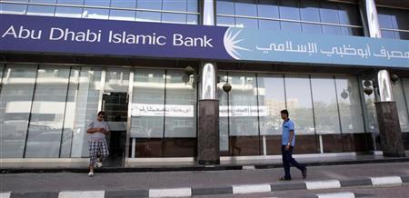 Men walk past a branch of Abu Dhabi Islamic Bank along Khalid Bin Al-Waleed Road in Dubai May 30, 2010.REUTERS/Mosab Omar