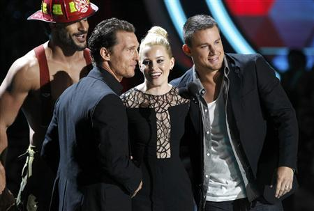 Actress Elizabeth Banks accepts the award for best on-screen transformation for her role in ''The Hunger Games'' from actors Joe Manganiello (L), Matthew McConaughey and Channing Tatum (R) at the 2012 MTV Movie Awards in Los Angeles, June 3, 2012. REUTERS/Mario Anzuoni