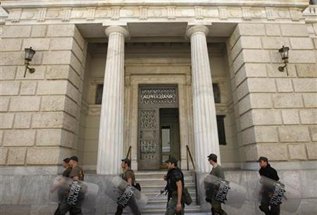 Riot police walk in front of the headquarters of Alpha bank in central Athens May 30, 2012. REUTERS/John Kolesidis