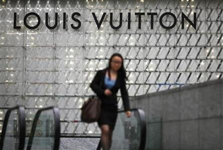A woman walks by a Louis Vuitton luxury boutique at the IFC Mall in Shanghai June 4, 2012. REUTERS/Carlos Barria