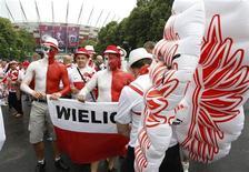 <p>Supporters polonais à leur arrivée au Stade national de Varvosie pour le match d'ouverture de l'Euro contre la Grèce. L'accès aux fonds de l'UE ont permis à la Pologne d'injecter 20 milliards d'euros dans les préparatifs de l'Euro. Ces 20 milliards représentent 5% du PNB annuel du pays, 30.000 emplois et un coup de pouce pour la croissance, au point que la Pologne a été la seule économie d'Europe à continuer de croître ces quatre dernières années. /Photo prise le 8 juin 2012/REUTERS/Jerzy Dudek</p>