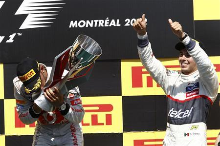 McLaren Formula One driver Lewis Hamilton (L) of Britain kisses his trophy next to third placed Sauber Formula One driver Sergio Perez of Mexico during the podium ceremony following the Canadian F1 Grand Prix at the Circuit Gilles Villeneuve in Montreal June 10, 2012. REUTERS/Chris Wattie