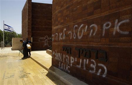 A worker uses a hose to clean graffiti sprayed at Yad Vashem Holocaust memorial in Jerusalem June 11, 2012. REUTERS/Ammar Awad