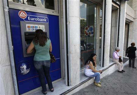 A woman (L) makes a transaction at an ATM machine outside a Eurobank branch in central Athens May 30, 2012. REUTERS/John Kolesidis