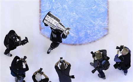 Los Angeles Kings' Jarret Stoll is pursued by photographers as he holds up the Stanley Cup after his team defeated the New Jersey Devils in Game 6 of the NHL Stanley Cup hockey final in Los Angeles, June 11, 2012. REUTERS/Lucy Nicholson