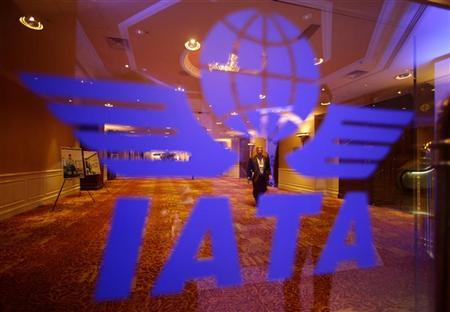 A delegate of the 68th International Air Transport Association (IATA) annual general meeting is pictured through an IATA logo in Beijing June 11, 2012. REUTERS/Jason Lee