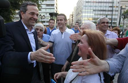 Conservative New Democracy party leader Antonis Samaras (L) is greeted by supporters outside an election campaign kiosk of his party in central Athens June 11, 2012. REUTERS/John Kolesidis
