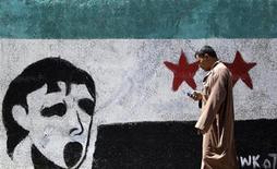 <p>Un hombre camina frente a un mural alusivo a Siria en El Cairo, jun 12 2012. Rebeldes en la ciudad siria asediada de Haffeh dicen que están intentando retirar clandestinamente a civiles atrapados después de que Estados Unidos advirtió de una masacre potencial en el bastión de la oposición. REUTERS/Amr Abdallah Dalsh</p>