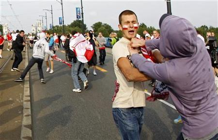 A Russian soccer fan (R) fights with a Polish supporter in Warsaw June 12, 2012. REUTERS/Peter Andrews