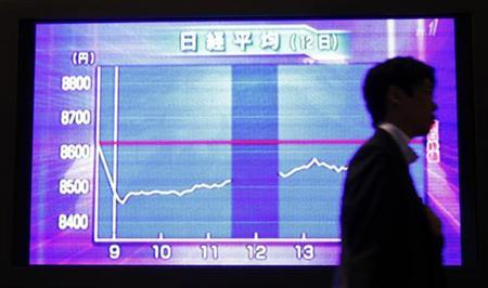 A man passes a television screen displaying a graph of Japan's Nikkei share average at a lobby of a brokerage in Tokyo June 12, 2012. REUTERS/Yuriko Nakao