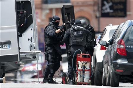 Special French GIPN intervention police prepare equipment at the scene where a man claiming to be a member of al Qaeda has taken hostages in a bank in Toulouse, June 20, 2012. The man took several hostages in a branch of French bank CIC and fired a shot after an attempted armed robbery apparently went wrong, a police union official reported. REUTERS/Bruno Martin