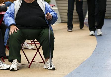 An overweight woman sits on a chair in Times Square in New York, May 8, 2012. America's obesity epidemic is so deeply rooted that it will take dramatic and systemic measures - from overhauling farm policies and zoning laws to, possibly, introducing a soda tax - to fix it, the influential Institute of Medicine said on Tuesday. REUTERS/Lucas Jackson