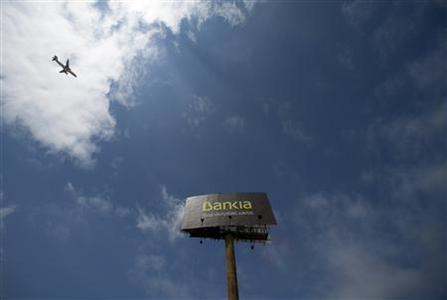 An aircraft flies over a billboard of Spain's lender bank Bankia on the outskirts of Seville June 21, 2012. REUTERS/Marcelo del Pozo