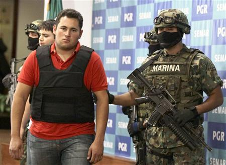 Mexican marines escort Jesus Alfredo Guzman (L), alias El Gordo, as he is presented to the media in Mexico City June 21, 2012. REUTERS/Henry Romero