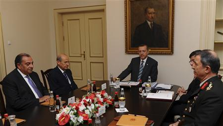 Turkish Prime Minister Recep Tayyip Erdogan (C) and Nationalist Movement Party (MHP) leader Devlet Bahceli (2nd L) are flanked by officials as they meet in Ankara June 24, 2012. Turkey accused Syria on Sunday of shooting down a military plane in international airspace without warning and called a NATO meeting to discuss a response to Syrian President Bashar al-Assad. Amid growing acrimony between the once-friendly neighbours, Syria said its forces had shot dead ''terrorists'' infiltrating its territory from Turkey, which along with Western and Arab nations has backed the cause of Syrians fighting Assad. REUTERS/Prime Minister's Press Office/Kayhan Ozer/Handout